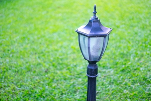 A lamp post against a green lawn.