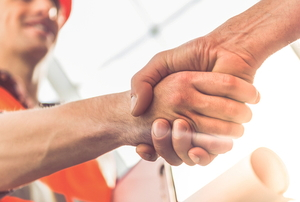 contractor in work gear shaking hands with someone