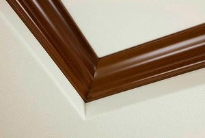 A corner of ceiling with brown crown molding.