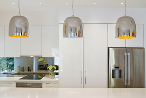 A trio of modern silver pendant lights hanging over a counter in a kitchen.