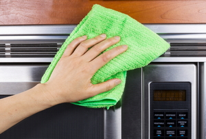 A stainless steel microwave and a cleaning rag.