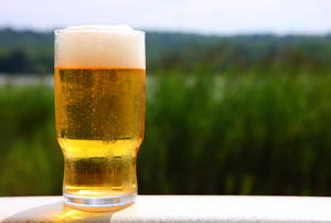 Foamy beer sitting on a white rail.