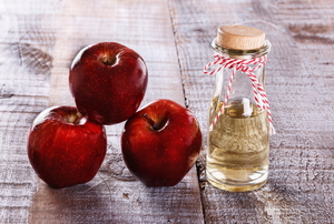 A trio of red apples next to a bottle of apple cider vinegar.