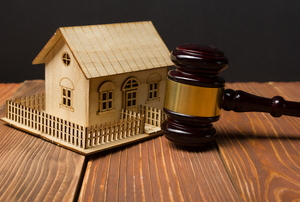 A small wood house and a gavel.