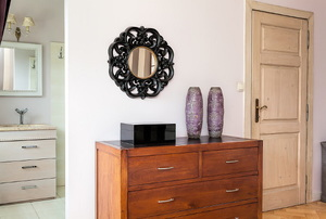 An entryway into an apartment with a dresser and a mirror above it.
