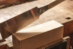 japanese two sided hand saw cutting a block of wood