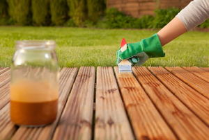 person staining deck boards