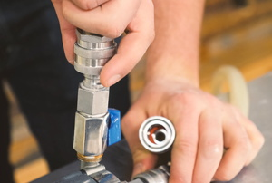 A person works on a ball valve.