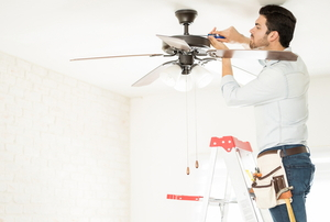 A man repairs a fan.