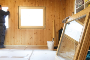 room under construction with wood paneling and glass windows