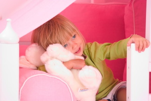 A little girl in a pink bed.