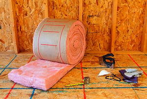 A roll of pink, fiberglass insulation with attendant tools in front of an unfinished wall.