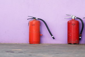 three fire extinguishers against a wall.