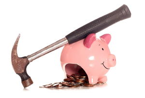 A broken piggy bank with coins spilling out and a hammer next to it.