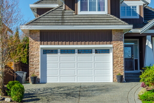 Home with white garage door and stone cladding accents