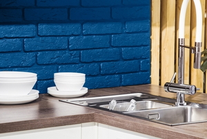 kitchen sink, coffee cups, and blue painted brick backsplash