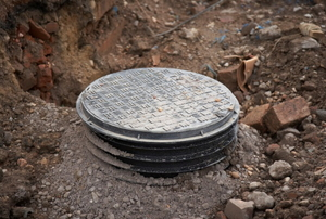A septic tank lid exposed outside of a home.