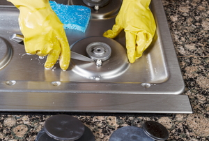 A pair of yellow gloves cleaning a metal stove top.