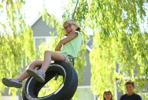 A girl having fun on a tire swing.