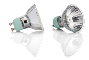 Two halogen light bulbs on a reflective white surface.