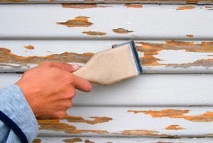 A man scraping an old garage that needs paint.