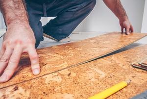 a man installing cork flooring