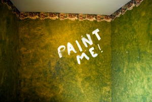An old wallpapered room with the words Paint Me on one wall