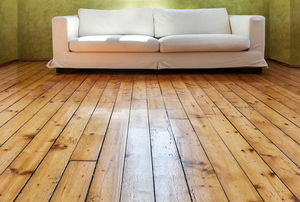 white couch in a room with reclaimed wood flooring