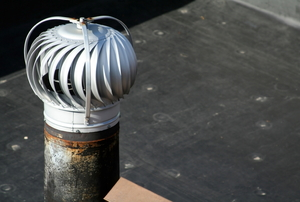A turbine vent on top of a flat roof.