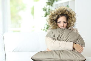 A woman wearing a furry coat and clutching blanket in a cold house.