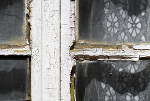 An old window frame with peeling paint and rotting wood.