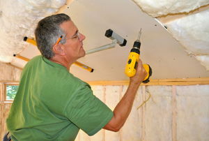 Drywall being applied to a ceiling.