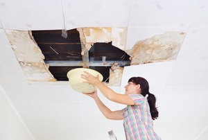 Woman with bucket under leaking ceiling