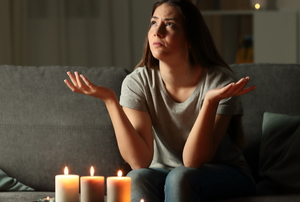 woman on couch in power outage with candles