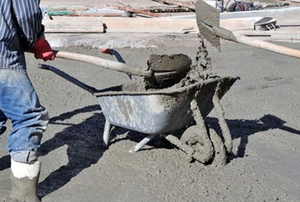 Two workers pouring concrete from a wheelbarrow.