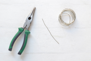A set of pliers with a wire cutter and roll of wire.