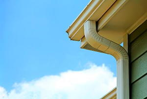 A from-under view of a soffit, gutter, and drain pipe on the corner of a house.