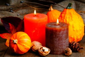 A cluster of Thanksgiving gourds and candles.