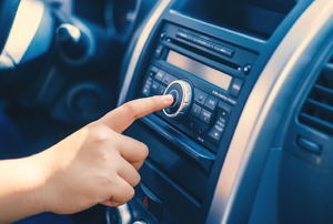 A finger pushing a button on a car radio.