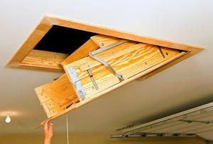 A hand pulling down an access door from a garage ceiling.