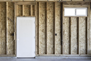 a framed wall in a garage with a white door
