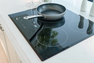 induction stove top with pan in stylish kitchen