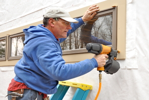A handyman installing a window on the exterior of a house with a nail gun and ladder.
