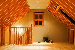 Looking down the length of a nearly-finished attic at a window and the foot of a staircase.