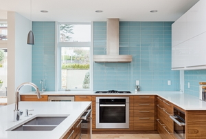 Large kitchen with white upper cabinets, wood lower cabinets and teal blue tile backsplash