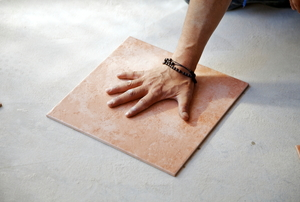 person's hand on a porcelain tile