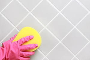 A gloved hand cleaning a shower wall with a sponge.