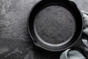 cast iron pan on stone background with cloth