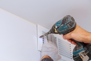 A man installs a window exhaust fan.