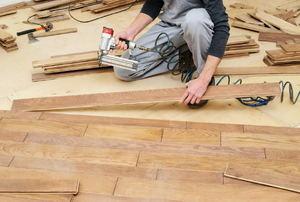 A man installs flooring.